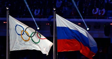 FILE - In this Feb. 23, 2014 file photo the Russian national flag, right, flies after it is hoisted next to the Olympic flag during the closing ceremony of the 2014 Winter Olympics in Sochi, Russia.