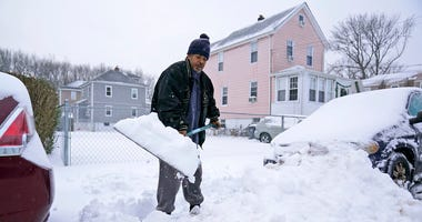 Barry James digs out his car, as well as his daughter's car, before trying to get to work in Englewood, N.J., Thursday, Dec. 17, 2020.