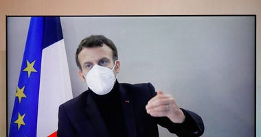 French President Emmanuel Macron is seen on a screen as he attends by video conference a round table for the National Humanitarian Conference (NHC), taken at the Foreign Ministry in Paris