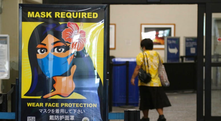 FILE - In this Oct. 2, 2020 file photo, a woman walks into the international airport in Honolulu amid a quarantine rule that effectively shut down the tourism industry in the state.