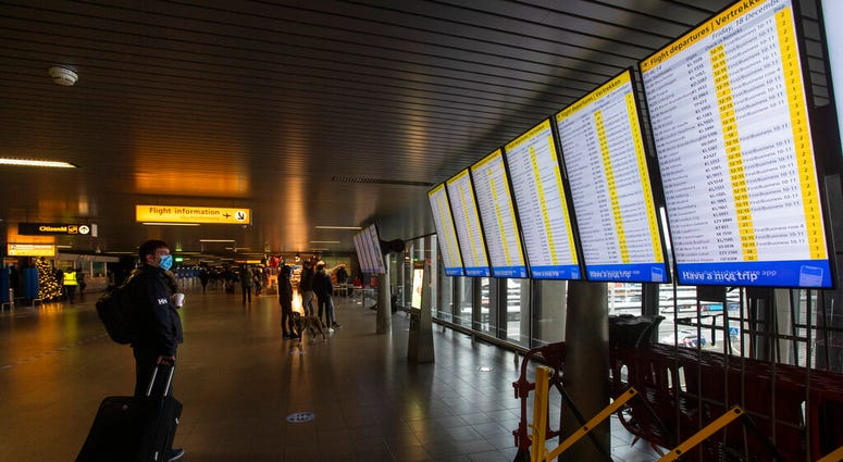 FILE- In this Friday Dec. 18, 2020, file photo, A traveller wearing a face mask checks the flight departures at Schiphol Airport, near Amsterdam, Netherlands.