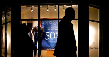 In this Saturday, Dec. 19, 2020 file photo, people walk past the window display of a store in Skokie, Ill. (AP Photo/Nam Y. Huh)