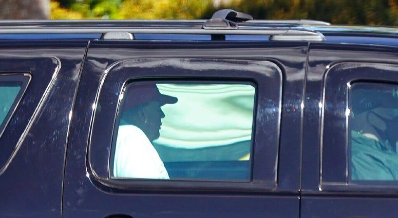 President Donald Trump rides in a motorcade vehicle as he departs Trump International Golf Club, Sunday, Dec. 27, 2020, in West Palm Beach, Fla. (AP Photo/Patrick Semansky)