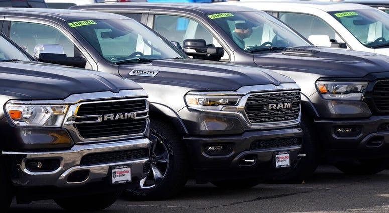 A long row of unsold 2020 pickup trucks sits at a Ram dealership Sunday, Dec. 27, 2020, in Littleton, Colo. (AP Photo/David Zalubowski)