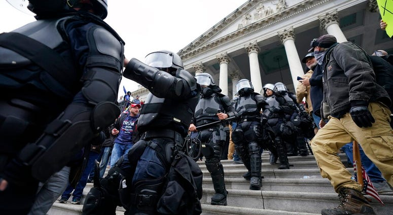 Police in riot gear walk out of the Capitol, Wednesday, Jan. 6, 2021, in Washington.