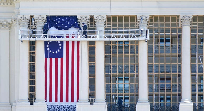 Workers install a flag on the West Front of the U.S. Capitol as preparations take place for President-elect Joe Biden's inauguration, Saturday, Jan. 9, 2021, in Washington.