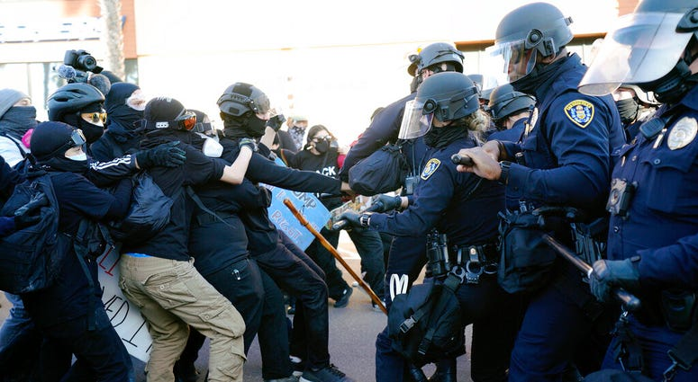San Diego police clash with protesters after a gathering was declared an unlawful assembly, Saturday, Jan. 9, 2021, in San Diego.