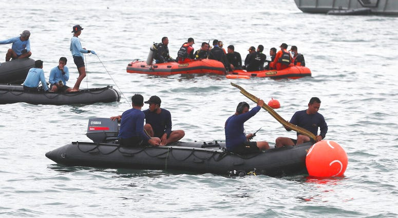 Rescuers carry debris found in the waters around the location where a Sriwijaya Air passenger jet has lost contact with air traffic controllers shortly after the takeoff, in Java Sea, near Jakarta, Indonesia,