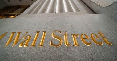 In this Nov. 5, 2020 file photo, a sign for Wall Street is carved in the side of a building. (AP Photo/Mark Lennihan, File)
