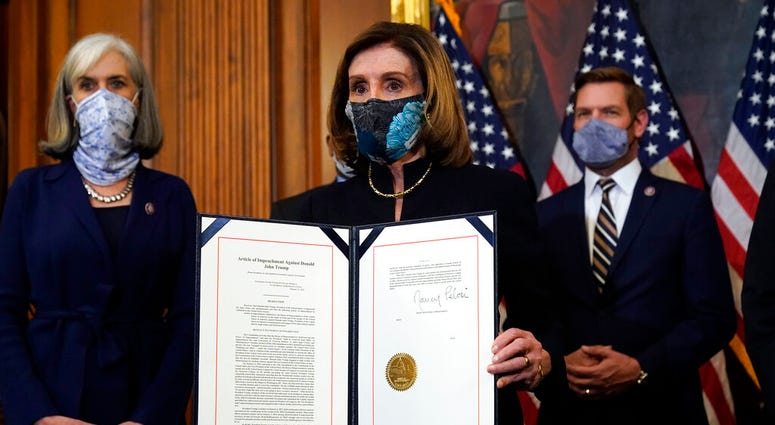 House Speaker Nancy Pelosi of Calif., displays the signed article of impeachment against President Donald Trump in an engrossment ceremony before transmission to the Senate for trial on Capitol Hill, in Washington. (AP Photo/Alex Brandon)