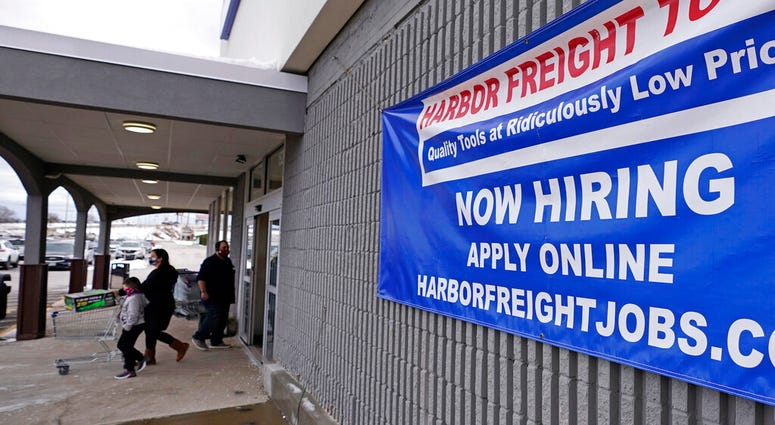 """In this Dec. 10, 2020, file photo, a """"Now Hiring"""" sign hangs on the front wall of a Harbor Freight Tools store in Manchester, N.H. (AP Photo/Charles Krupa, File)"""
