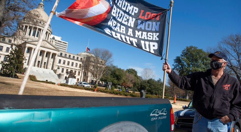Dale Gibson, of Jackson, Miss., shows off the banner he planned to hold as a counter-protester if a pro-Trump rally materialized Sunday, Jan. 17, 2021.