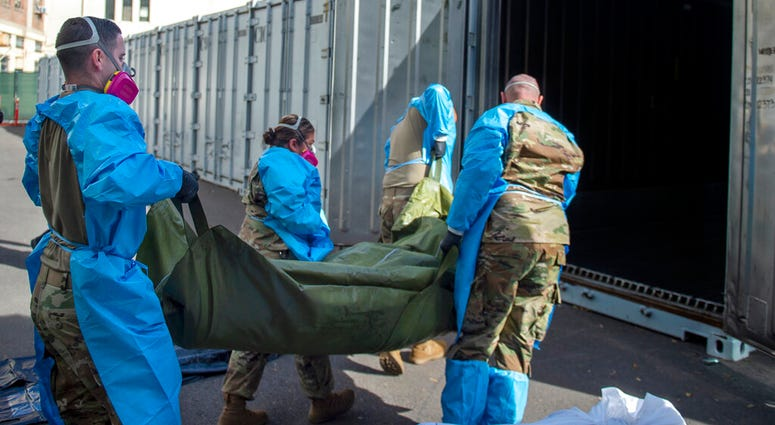 In this Jan. 12, 2021 photo provided by the Los Angeles County Department of Medical Examiner-Coroner, National Guard members assisting with processing COVID-19 deaths, placing them into temporary storage at the medical examiner-coroner's office in L.A.