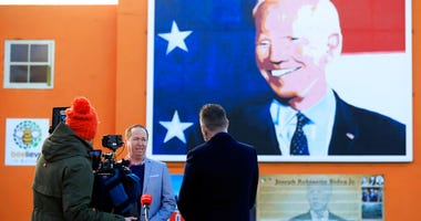 Joe Biden's cousin Joe Blewitt speaks to the media underneath his mural painted on a wall in Ballina, Ireland, Wednesday, Jan. 20, 2021. (AP Photo/Peter Morrison)