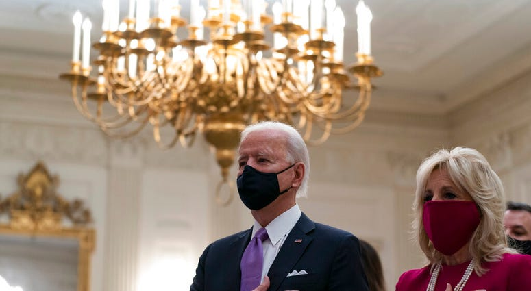 President Joe Biden, accompanied by first lady Jill Biden, places his hand over his heart during a performance of the national anthem, during a virtual Presidential Inaugural Prayer Service.  (AP Photo/Alex Brandon)