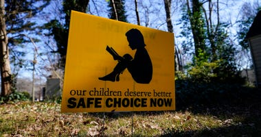 "A sign that reads ""our children deserve better safe choice now"" is seen on Friday, Jan. 15, 2021, in Decatur, Ga. (AP Photo/Brynn Anderson)"