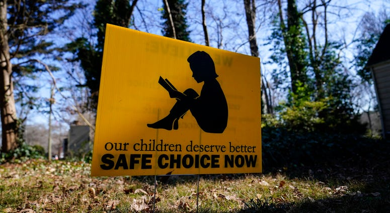 """A sign that reads """"our children deserve better safe choice now"""" is seen on Friday, Jan. 15, 2021, in Decatur, Ga. (AP Photo/Brynn Anderson)"""