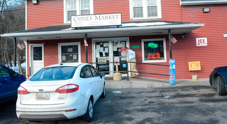 A patron approaches the entrance to Coney Market, a convenience store Lonaconing, Md., where the jackpot-winning Powerball ticket worth $731.1 million was sold in a struggling coal mining town.  (Steven Bittner/Cumberland Times-News via AP)