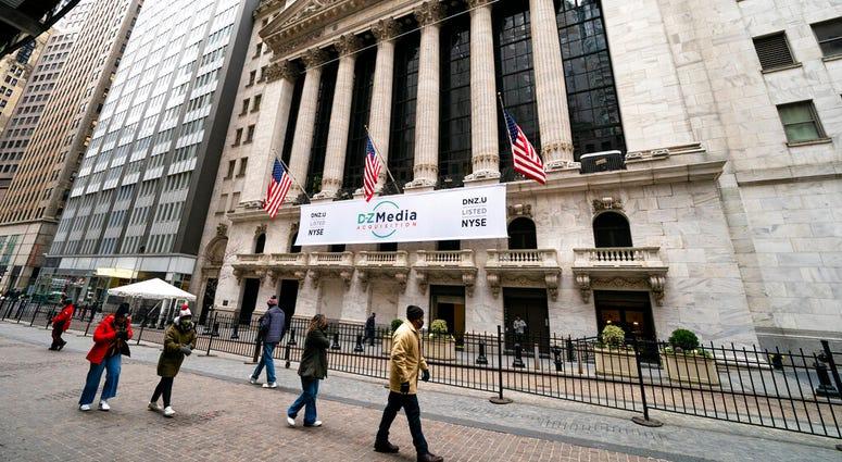 Pedestrians pass the New York Stock Exchange, Wednesday, Jan. 27, 2021, in New York. (AP Photo/John Minchillo)