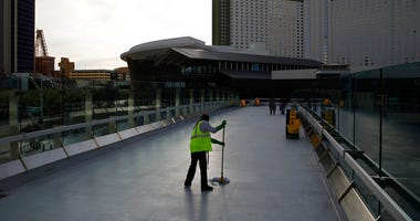 FILE - In this March 31, 2020, file photo, a worker cleans along the Las Vegas Strip devoid of the usual crowds as casinos and other business are shuttered due to the coronavirus outbreak in Las Vegas.   (AP Photo/John Locher, File)