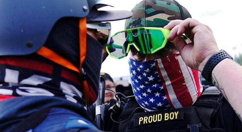 FILE - In this Sept. 26, 2020, file photo, member of the Proud Boys, right, stands in front of a counter protester as members of the Proud Boys and other right-wing demonstrators rally, in Portland.