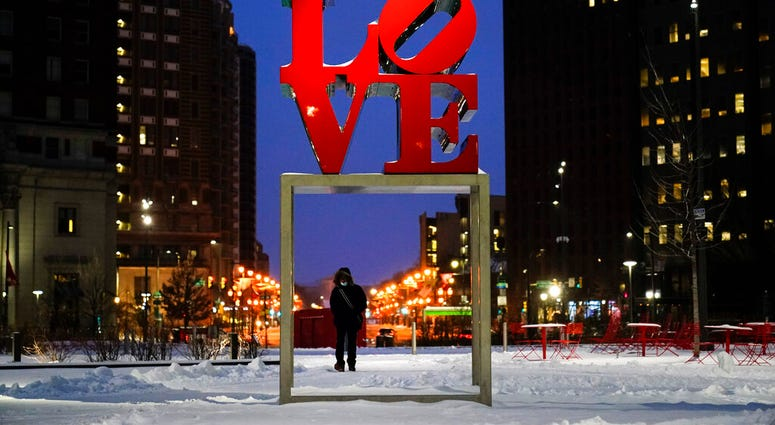 "A person wearing a face mask as a precaution against the coronavirus walks during a winter storm near the Robert Indiana sculpture ""LOVE"" at John F. Kennedy Plaza, commonly known as Love Park, in Philadelphia, Monday, Feb. 1, 2021."