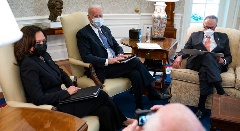 Vice President Kamala Harris, President Joe Biden, and Senate Majority Leader Sen. Chuck Schumer of N.Y., during a meeting to discuss a coronavirus relief package, in the Oval Office of the White House, Wednesday, Feb. 3, 2021, in Washington.