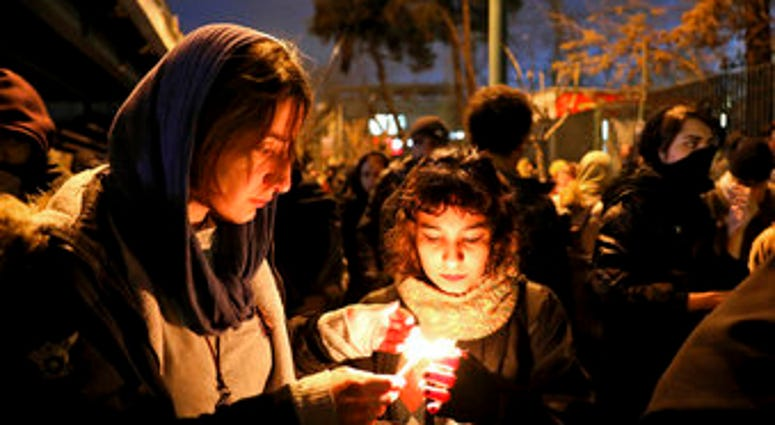 eople gather for a candlelight vigil to remember the victims of the Ukraine plane crash, at the gate of Amri Kabir University that some of the victims of the crash were former students of, in Tehran, Iran. (AP Photo/Ebrahim Noroozi)