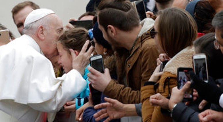 Pope Francis kisses a child in St. Peter's Square at the Vatican before leaving after his weekly general audience, Wednesday, Feb. 26, 2020. (AP Photo/Alessandra Tarantino)
