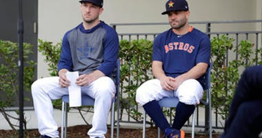 Houston Astros infielder Alex Bregman, left, and Jose Altuve sit in chairs as they wait to deliver statements during a news conference before the start of the first official spring training baseball practice for the team Thursday. (AP Photo/Jeff Roberson)