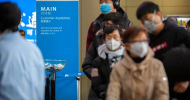 Travelers wearing face masks line up to check in for an American Airlines flight to Los Angeles at Beijing Capital International Airport in Beijing, Thursday, Jan. 30, 2020. (AP Photo/Mark Schiefelbein)