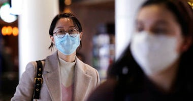 Travelers at Seattle-Tacoma International Airport wear masks Tuesday, March 3, 2020, in SeaTac, Wash. (AP Photo/Elaine Thompson)