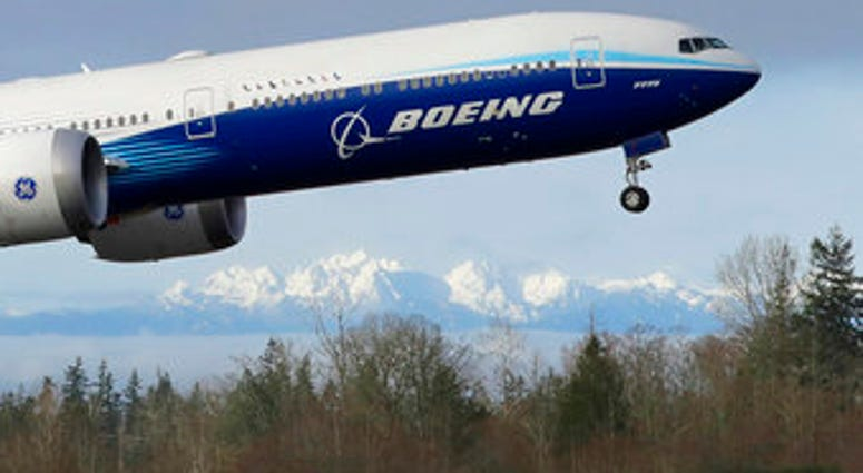 FILE - In this Jan. 25, 2020, file photo a Boeing 777X airplane takes off on its first flight with the Olympic Mountains in the background at Paine Field in Everett, Wash. (AP Photo/Ted S. Warren, File)