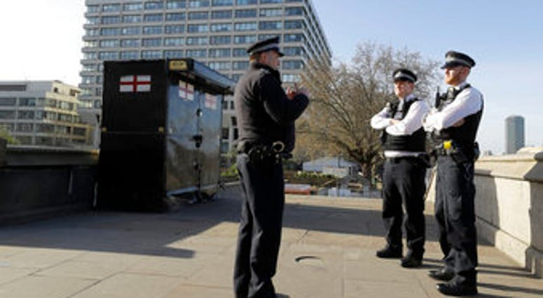 Police officers stand outside St Thomas' Hospital in central London as British Prime Minister Boris Johnson was moved to intensive care after his coronavirus symptoms worsened in London, Tuesday, April 7, 2020. (AP Photo/Kirsty Wigglesworth)
