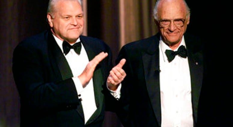 FILE - In this June 6, 1999 file photo, actor Brian Dennehy, left, applauds playwright, Arthur Miller, before awarding him the Lifetime Achievement Award at the Tony Awards in New York. (AP Photo/Kathy Willens, File)