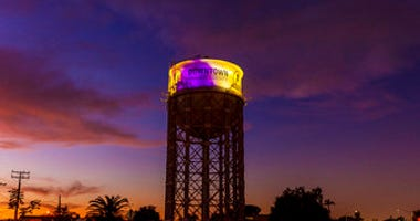 The historic 1928 Santa Ana water tower in Santa Ana, Calif., Monday, Jan. 27, 2020, is illuminated in purple and gold light in remembrance of Los Angeles Lakers legend Kobe Bryant. (Leonard Ortiz/The Orange County Register via AP)