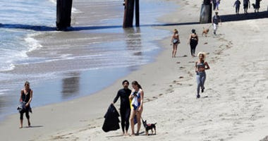 FILE - In this Wednesday, May 13, 2020, file, photo beachgoers walk and exercise on the beach in Malibu, Calif. Masks are required at Los Angeles County beaches, which reopened Wednesday. (AP Photo/Marcio Jose Sanchez, File)