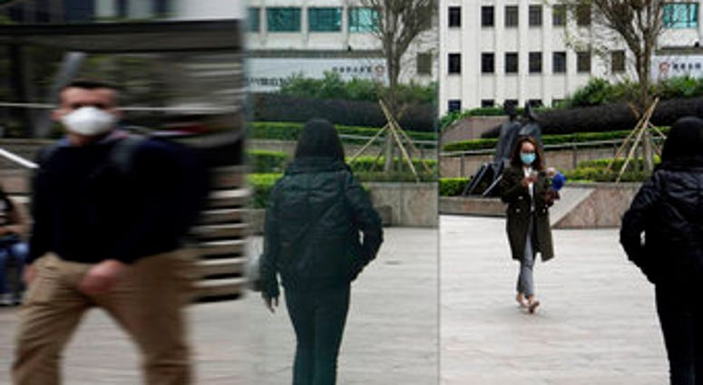 People wearing protective face masks, walk on a street in the Central, the business district of Hong Kong, Tuesday, Feb. 11, 2020. (AP Photo/Kin Cheung)