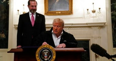 President Donald Trump signs an $8.3 billion bill to fight the coronavirus outbreak in the U.S., Friday, March 6, 2020 at the White House in Washington, as Department of Health and Human Services Secretary Alex Azar, looks on. (AP Photo/Evan Vucci)