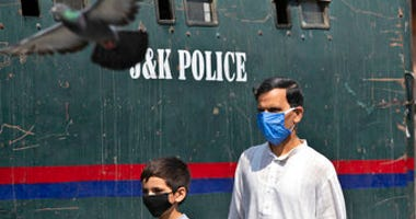 A Kashmiri man and a child wearing masks walk past a parked armored police vehicle in Srinagar, Indian controlled Kashmir, Monday, July 13, 2020. (AP Photo/Mukhtar Khan)