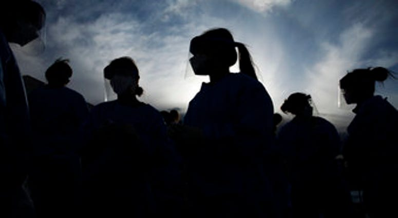In this Saturday, March 28, 2020 file photo, medical and physician assistant students wear personal protective equipment as they prepare to screen for possible coronavirus cases at a makeshift camp for the homeless in Las Vegas.(AP Photo/John Locher)