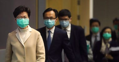 Hong Kong Chief Executive Carrie Lam, front, and other government officials wear protective face masks before a press conference in Hong Kong, Friday, Jan. 31, 2020. (AP Photo/Achmad Ibrahim)