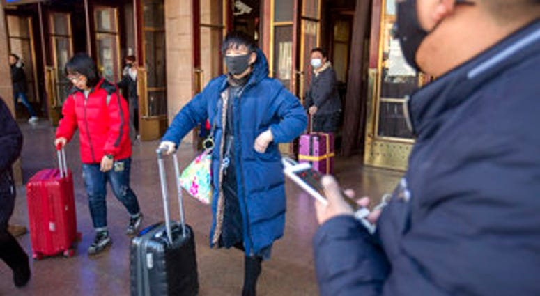 Travelers wear face masks as they walk outside of the Beijing Railway Station in Beijing, Monday, Jan. 20, 2020. China reported Monday a sharp rise in the number of people infected with a new coronavirus. (AP Photo/Mark Schiefelbein)
