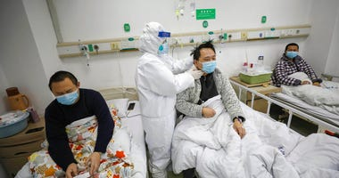 A doctor checks the conditions of a patient in Jinyintan Hospital, designated for critical COVID-19 patients, in Wuhan in central China's Hubei province Thursday, Feb. 13, 2020. (Chinatopix Via AP)