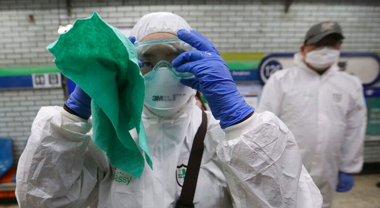 A worker wearing protective gears adjusts her glasses while she prepares to spray disinfectant as a precaution against the coronavirus at a subway station in Seoul, South Korea, Friday, Feb. 21, 2020. (AP Photo/Ahn Young-joon)