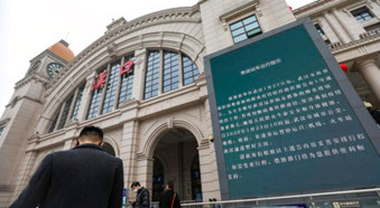 People walk past a billboard announcing the closure of the Hankou Railway Station in Wuhan in central China's Hubei Province, Thursday, Jan. 23, 2020. (Chinatopix via AP)