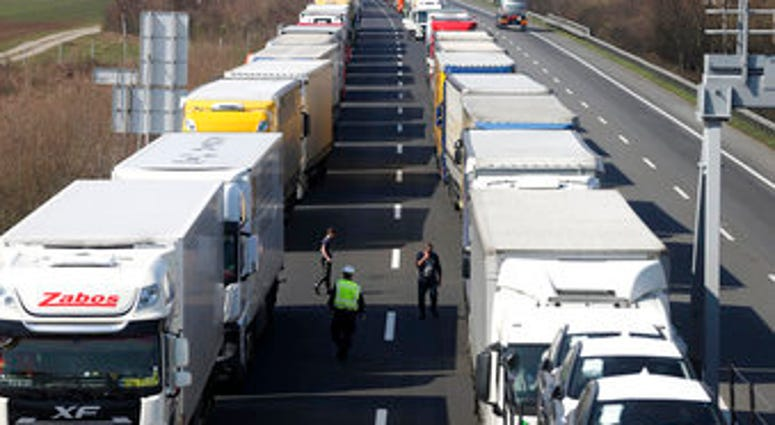 Trucks stand on the highway close to the border between Austria and Hungary near Bruck an der Leitha, Austria, Wednesday, March 18, 2020. (AP Photo/Ronald Zak)