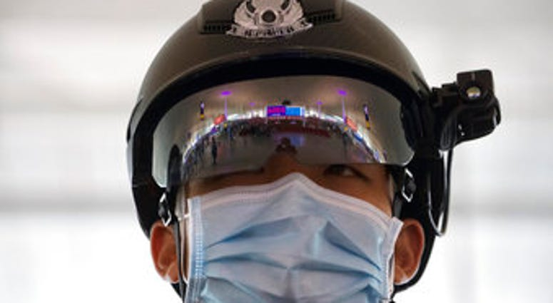 A police officer wearing a face mask to protect against the spread of new coronavirus stands guard at Wuhan Tianhe International Airport in Wuhan in central China's Hubei Province. (AP Photo/Ng Han Guan)