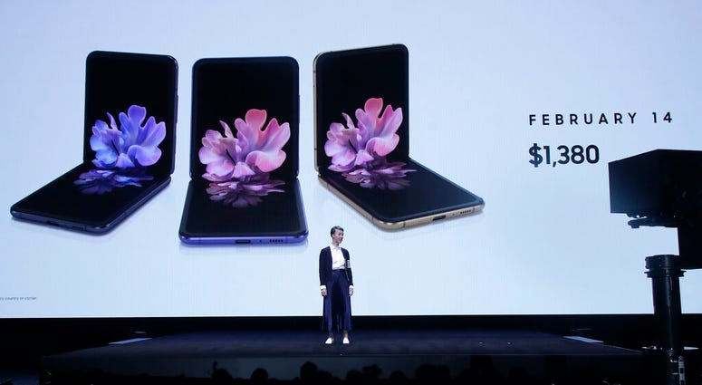 Rebecca Hirst, head of UK Mobile Product Development, speaks in front of photos of Samsung Galaxy Z Flip Phones at the Unpacked 2020 event in San Francisco, Tuesday, Feb. 11, 2020. (AP Photo/Jeff Chiu)