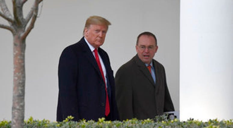 FILE - In this Jan. 13, 2020. file photo, President Donald Trump, left, and acting White House chief of staff Mick Mulvaney, right, walk along the colonnade of the White House in Washington. (AP Photo/Susan Walsh, File)